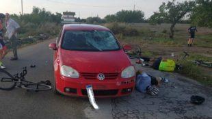 Imagen del vehículo y los ciclistas heridos en el suelo.