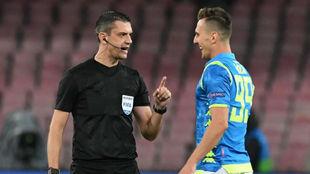 Viktor Kassai dialoga con Milik durante el partido.