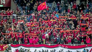 Aficionados chinos alientan durante un partido de fútbol