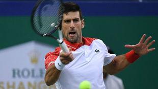Djokovic hits a return against  Zverev during their men's singles...