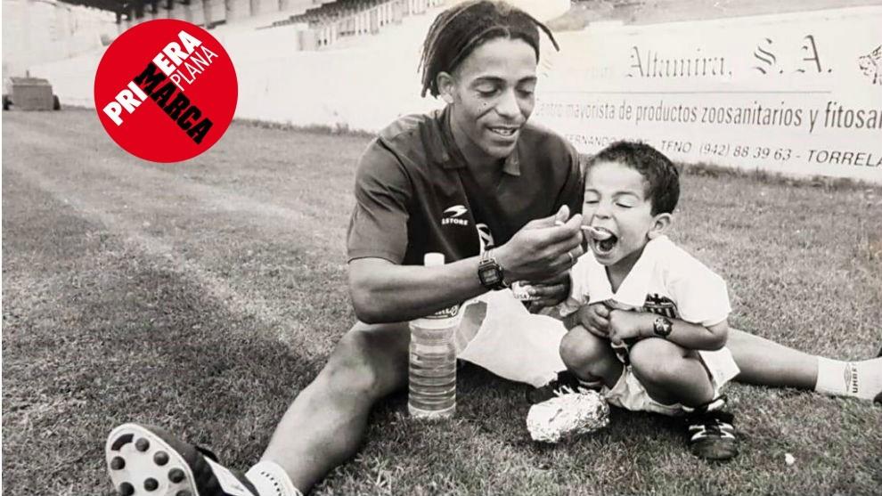 Óscar Engonga, dando de comer sobre el césped a su hijo Igor.