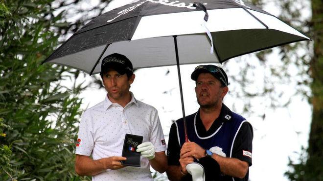 Grégory Bourdoy, se resguarda de la lluvia bajo el paraguas.