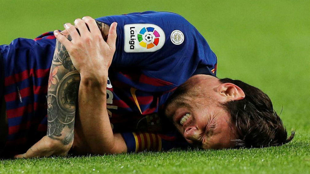 Messi gestures in pain during the Spanish league football match FC...