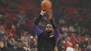 LeBron James tira a canasta en el calentamiento del partido entre...