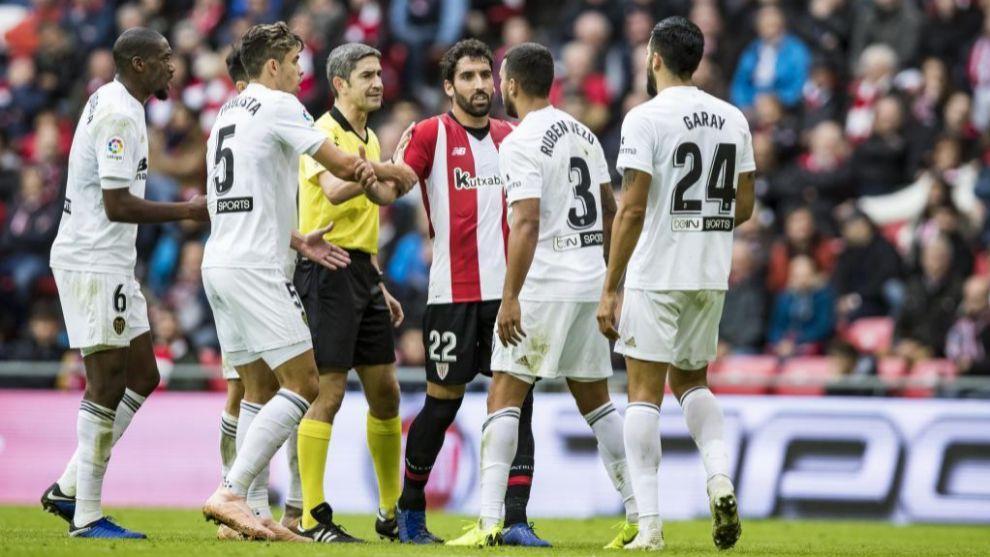 Raúl García, entre varios jugadores del Valencia que protestan ante...