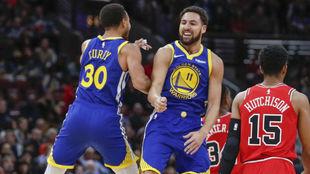 Stephen Curry y Klay Thompson celebran uno de los 14 triples del...