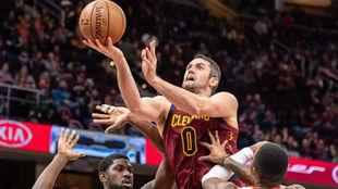 Kevin Love intenta levantar el balón ante la defensa de los Hawks