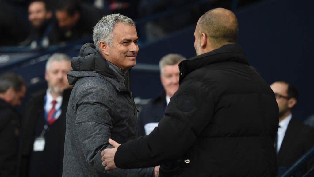Mourinho is greeted by  Guardiola as they arrive for the match between...