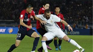 Karim Benzema batalló para superar a la defensiva japonesa.
