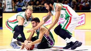 Jaime Fernández lucha por un balón con dos jugadores del Banvit.