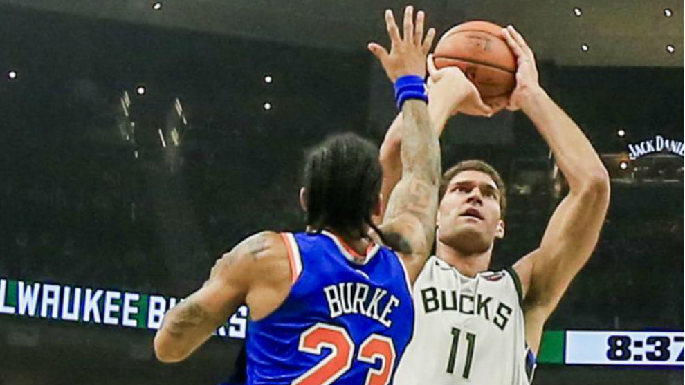 Brook López lanza ante la defensa de Trey Burke.