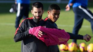 Gonalons se pone un peto en un entrenamiento, con Muriel al lado.