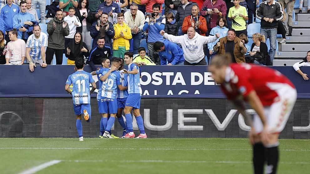Los jugadores del Málaga celebran el gol del triunfo ante un abatido...