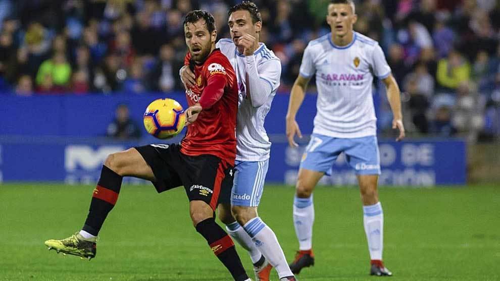 Álex López controla el balón ante la presión de Lasure en La Romareda