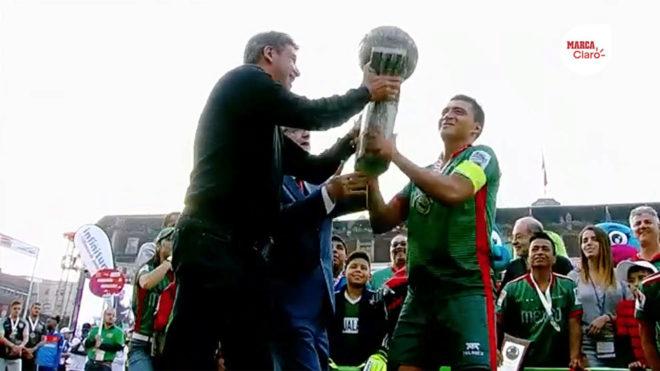 Entrega el trofeo a los jugadores mexicanos.