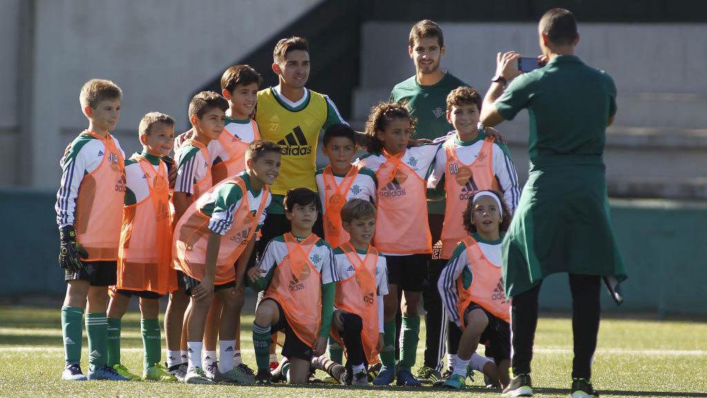Varios niños de la cantera del Betis posan con dos jugadores del primer equipo.