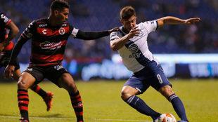 Lucas Cavallini intenta quitarse a Juan Carlos Valenzuela.