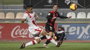 Ricardo Vaz intenta centrar ante la oposición del capitán visitante...
