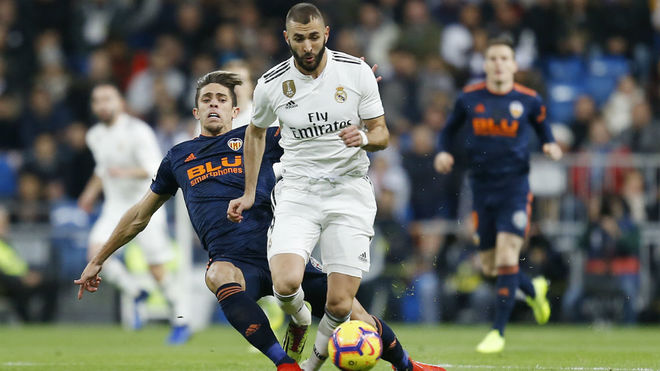 Benzema y Gabriel Paulista pelean por un balón.