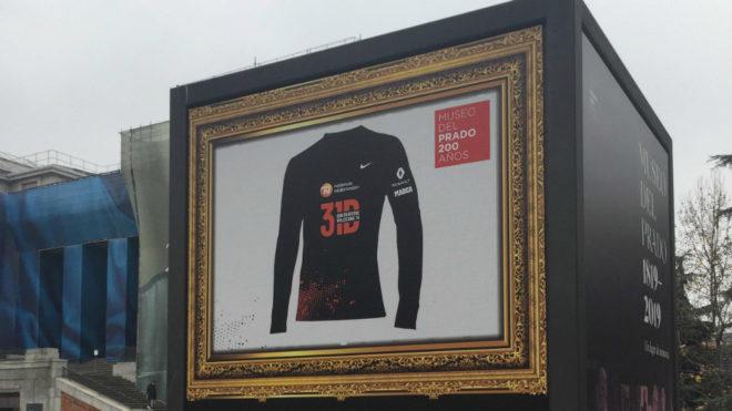 Tótem publicitario con la camiseta de la carrera junto a la puerta...