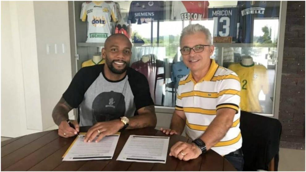 Maicon signing his contract with Criciuma president Jaime Dal Farra.