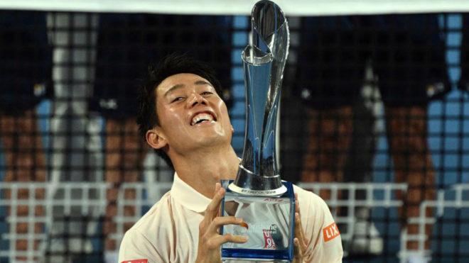 Kei Nishikori sonríe al posar con su primer trofeo en casi tres...
