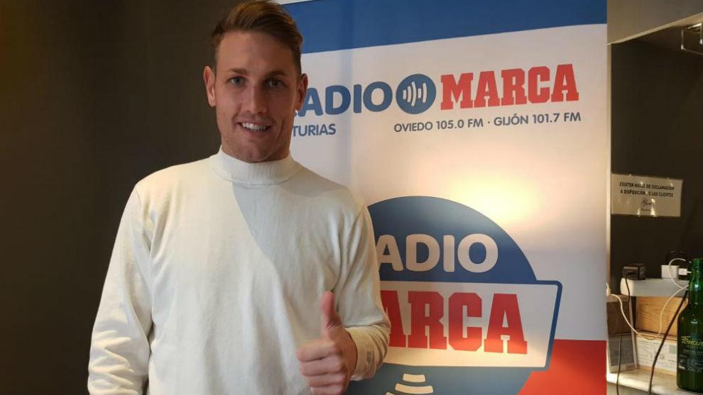 Carlos Hernández posa sonriente delante del logo de radio MARCA