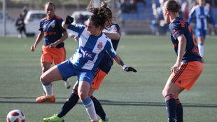 Paula Moreno, jugadora del Espanyol, puja por el balón con dos...