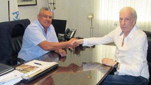 Claudio tapia y César Luis menotti se dan la mano.