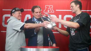 Tom Brady y Bill Belichick reciben el trofeo de campeones de la AFC.