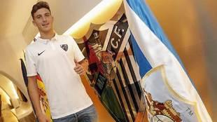 Pau Torres   posa delante de un escudo del Málaga haciendo la señal...