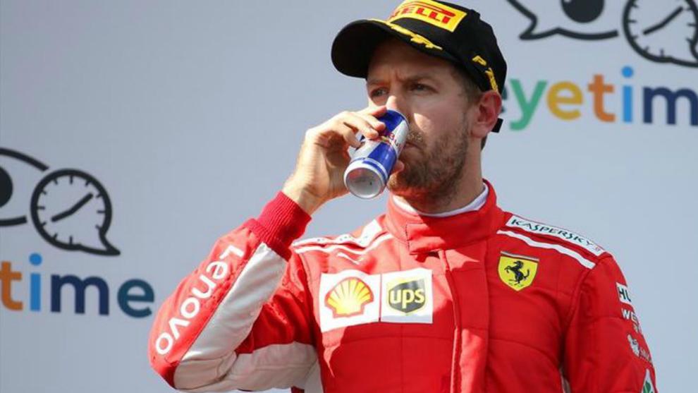 Vettel bebe de una lata de Red Bull en el podio del GP de Austria.