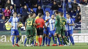 Keidi Bare y el colegiado Ocón Arráiz, rodeados por varios jugadores...