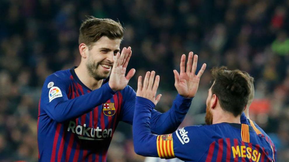 Piqué celebrates with Messi.