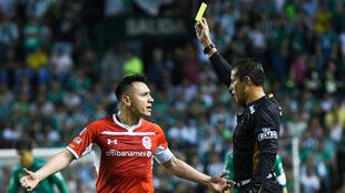 El árbitro le muestra una tarjeta amarilla.