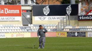 Un empleado del Reus cuida el césped del estadio municipal.