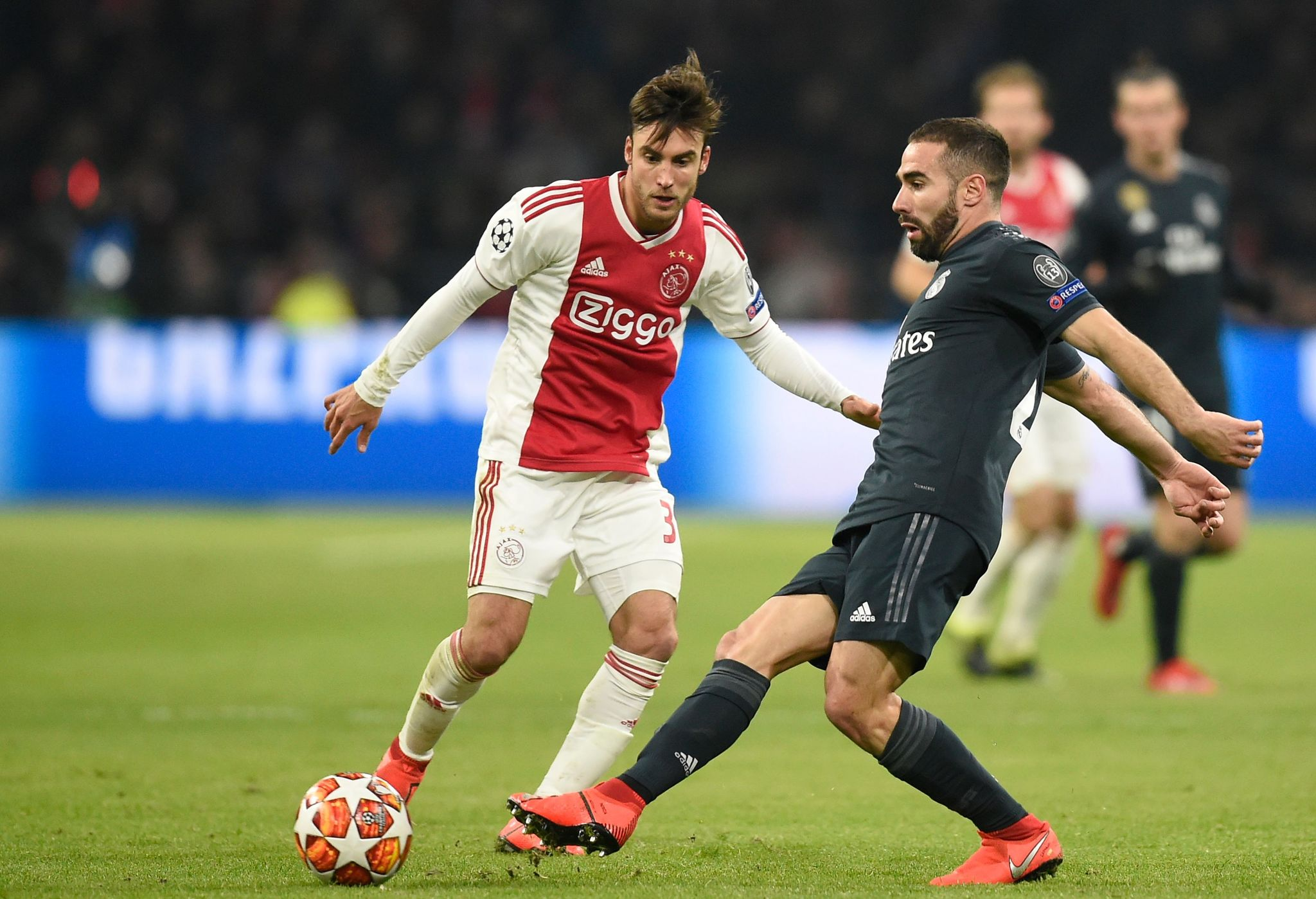Ajaxs Argentine defender Nicolas <HIT>Tagliafico</HIT> (L) fights for the ball with Real Madrids Spanish defender Dani Carvajal during the UEFA Champions league round of 16 first leg football match between Ajax Amsterdam and Real Madrid at the Johan Cruijff ArenA on February 13, 2019. (Photo by JOHN THYS / AFP)