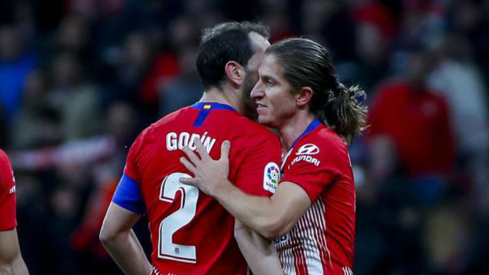 Godín y Filipe se abranzan durante un partido.