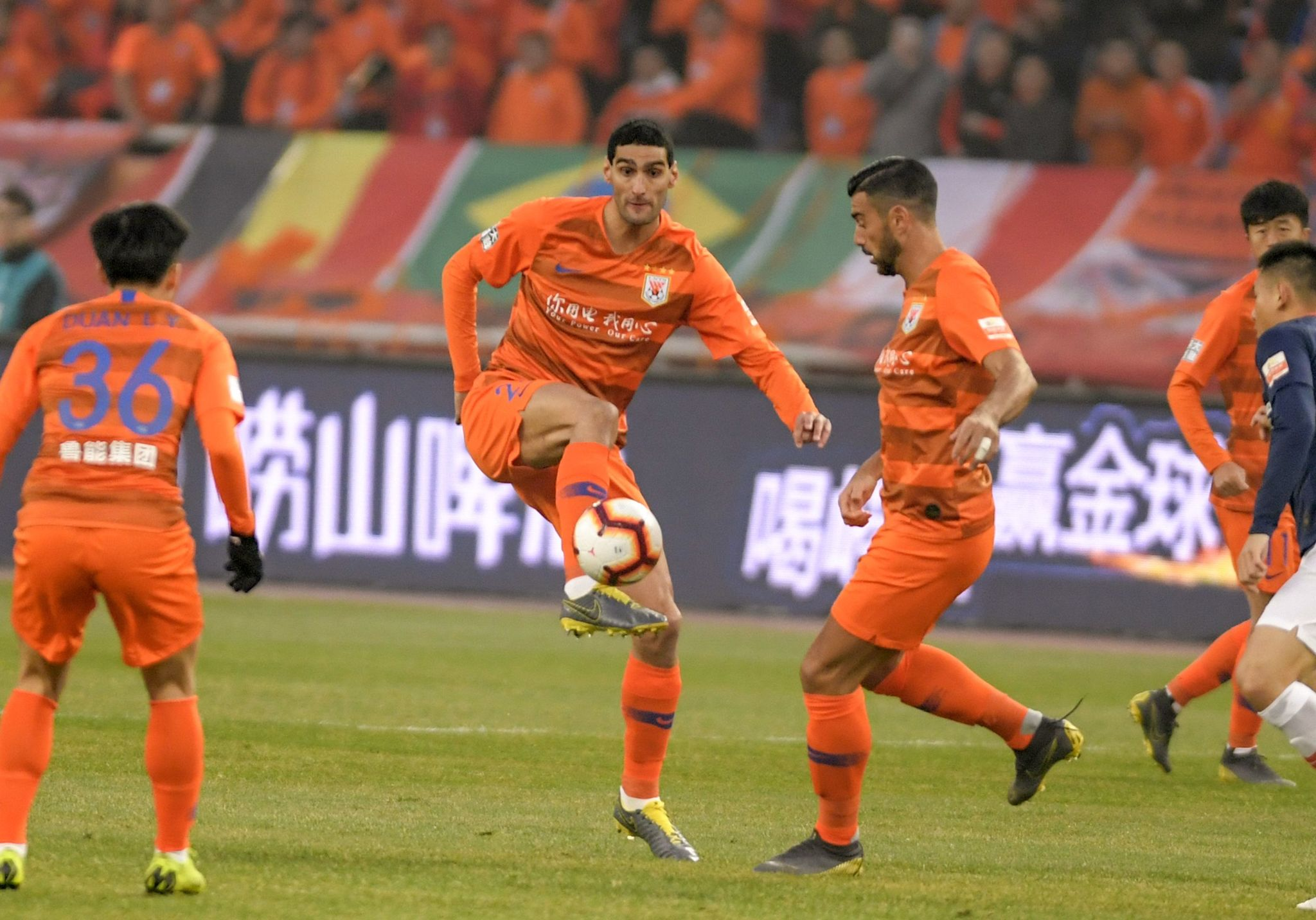 Marouane <HIT>Fellaini</HIT> (C) of Shandong Luneng kicks the ball next to teammate Graziano Pelle (R) during the Chinese Super League (CSL) football match between Shandong Luneng and Beijing Renhe in Jinan in Chinas eastern Shandong province on March 1, 2019. - Marouane <HIT>Fellaini</HIT> needed just 50 minutes to make his mark in Chinese football, scoring the winner on his debut for Shandong Luneng on March 1 following his move from Manchester United. (Photo by STR / AFP) / China OUT