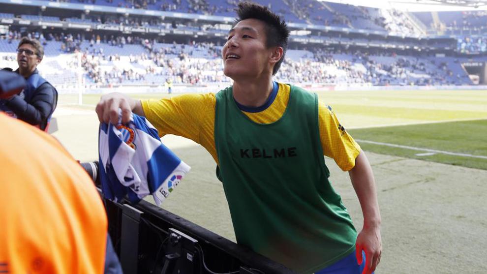 Wu Lei entrega su camiseta a unos aficionados.