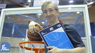 Moncho Fernández, apoyado en una canasta con un balón y su pizarra.