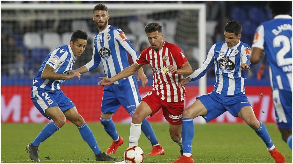 Juan Carlos Real  intenta llevarse el balón entre Vicente Gómez y...