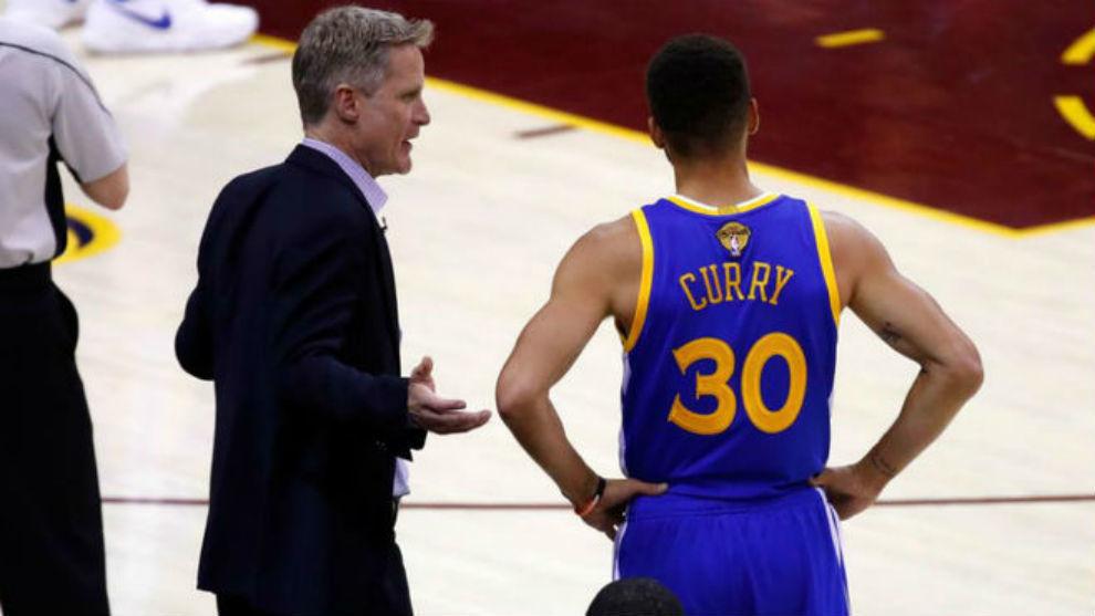 Steve Kerr charla con Curry durante un partido