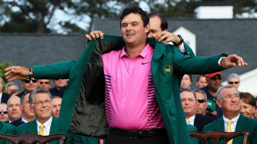 Patrick Reed, campeón en 2018, recibe la chaqueta de manos de Sergio...