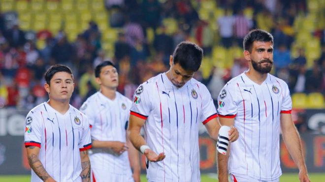 Jugadores de Chivas caminan cabizbajos.