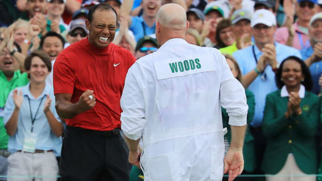 Tiger celebra con su caddie el triunfo en el Masters de Augusta.