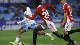 James Igbekeme trata de marcharse de dos rivales.