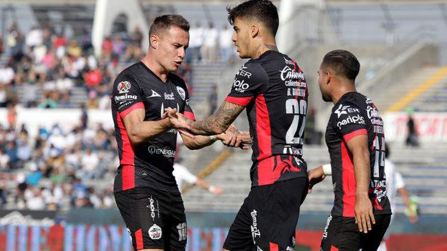 Jugadores de Lobos BUAP festejan un gol ante Pumas.
