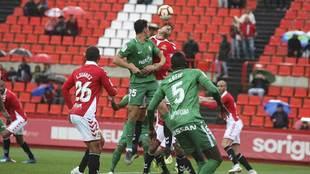 Jugadores de ambos equipos buscan un balón aéreo en el Nou Estadi