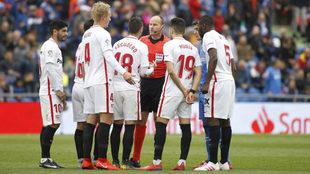 Los jugadores del Sevilla protestan la expulsión de Escudero.